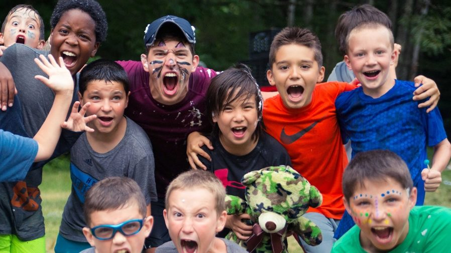 Young male campers with facepaint screaming