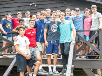 Boys standing on a cabin porch