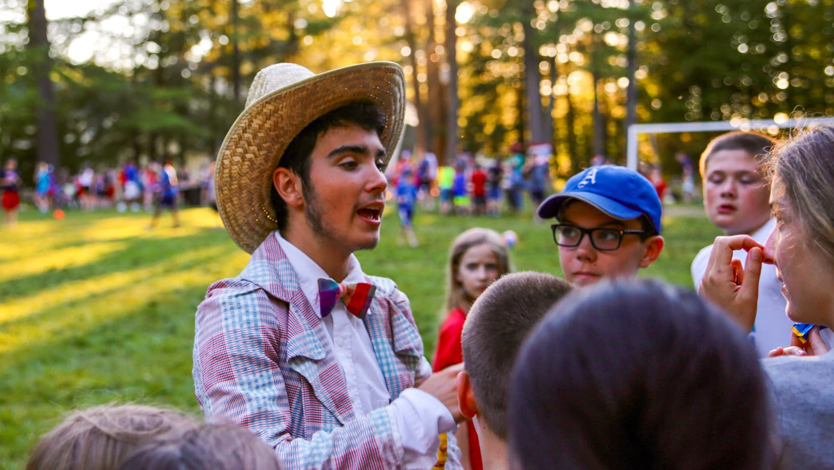 Staff talking with campers while wearing a cowboy hat