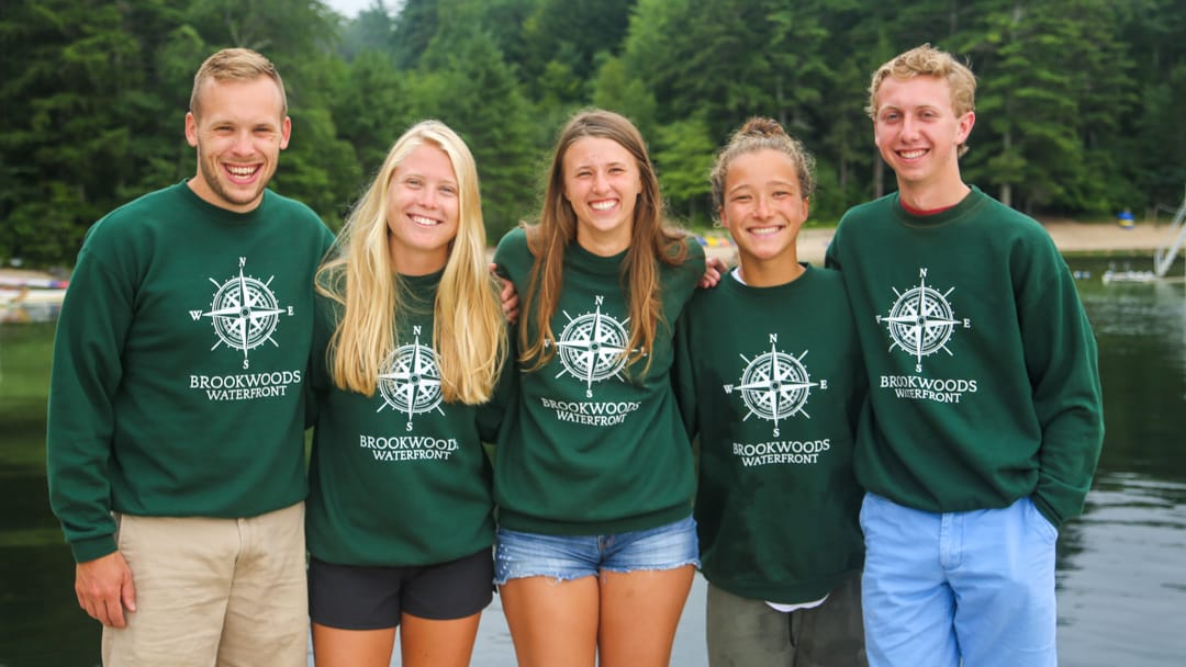 Five camp staff wearing Brookwoods sweatshirts by the lake