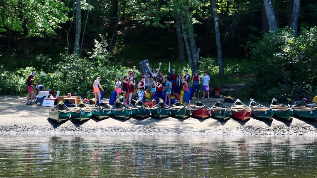 Campers standing by canoes