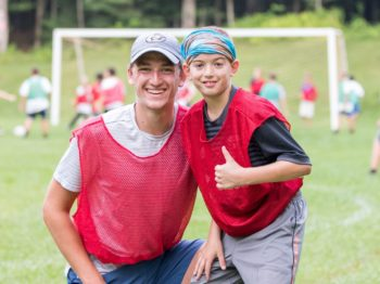 Camper and staff smiling at soccer