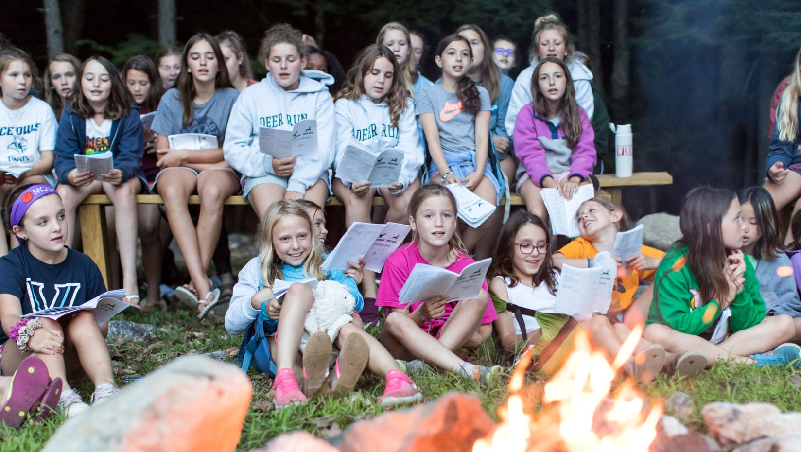 Deer Run campers singing worship songs by a campfire