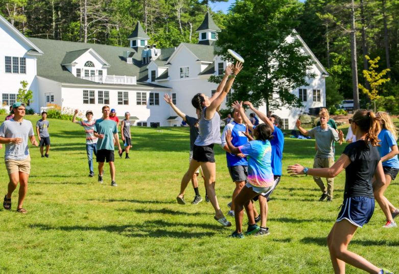 Campers playing frisbee on the front lawn