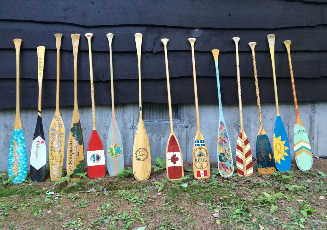 Decorated paddles leaning on a cabin on the Leadership Development Program