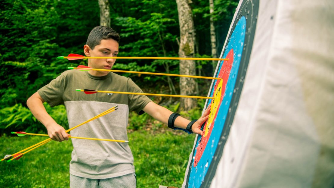 camper pulling out archery arrows from target