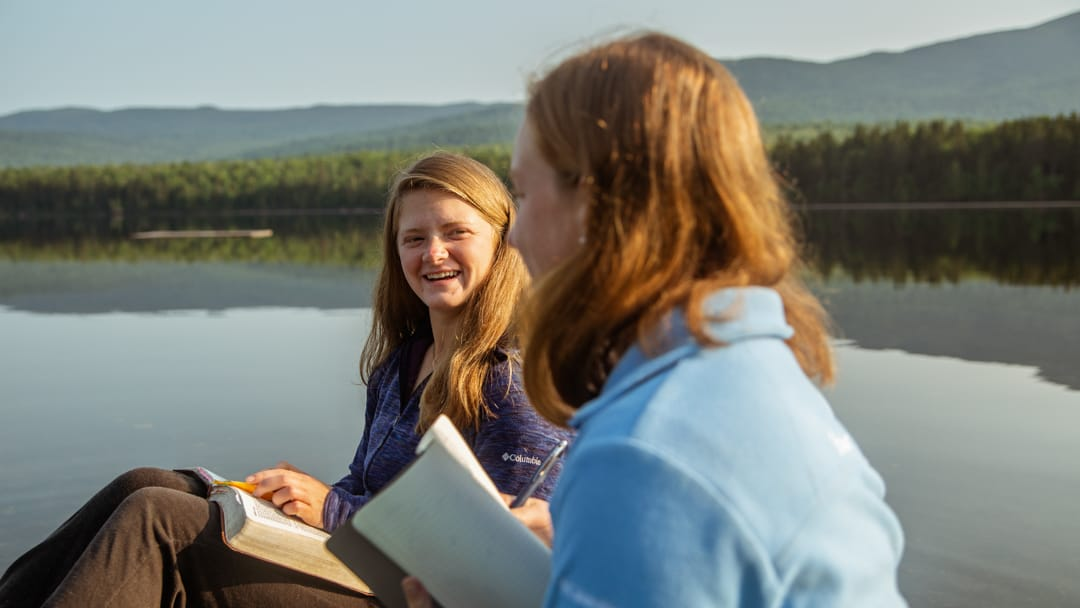 two girls reading bibles by the lake