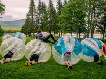 Camper laying on four giant bubble soccer balls
