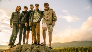 Five boys standing on a rock by the lake