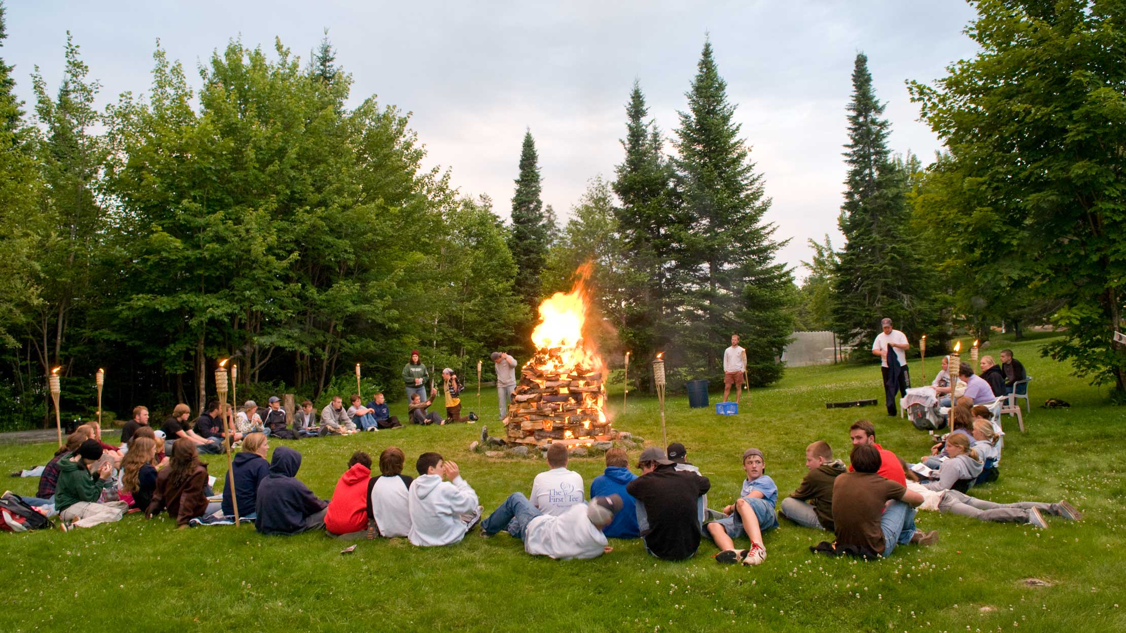 Campers and staff sitting around a campfire