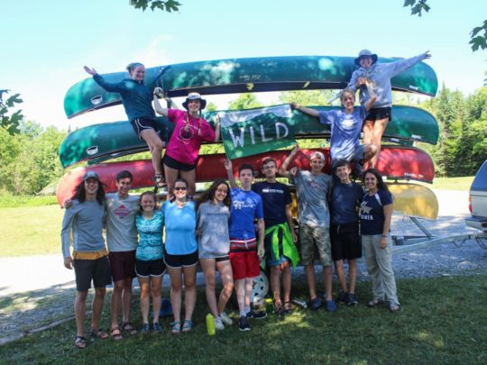 group standing by stacked canoes