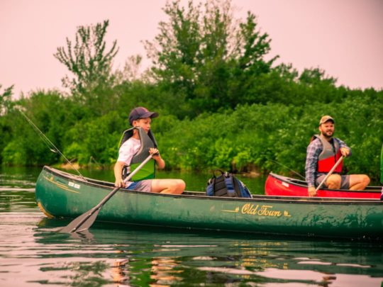 Staff and camper canoeing on a lake