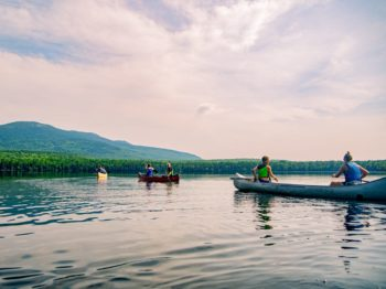 Campers canoeing on the lake at Moose River Outpost with mountains in the background