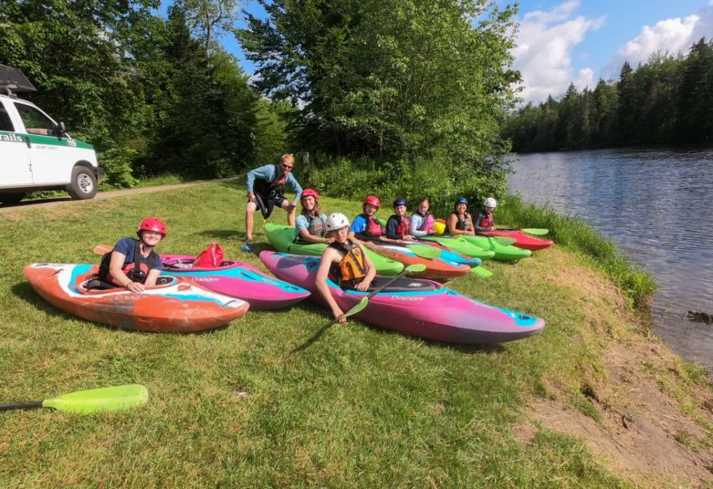 Campers sitting in white water kayaks with staff standing nearby