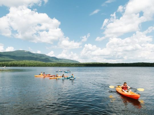 Campers and staff kayaking on a lake