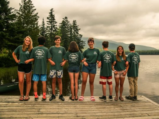 Campers wearing matching shirts and linking arms by the lake