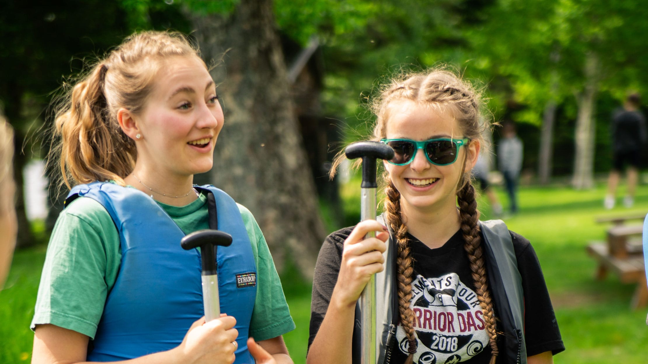 Two girls talking while holding paddles