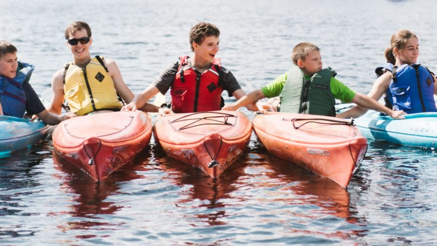 Five campers in kayaks holding onto each other and smiling