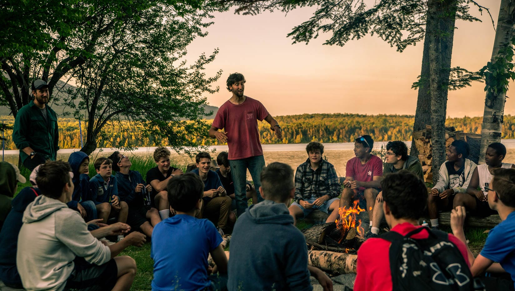Staff leading a campfire circle at sunset
