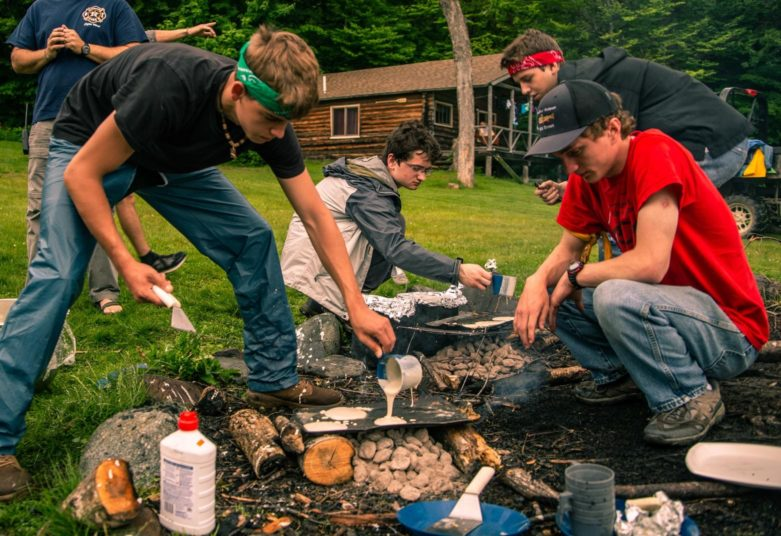 Campers building a campfire at Moose River Outpost