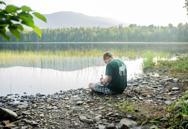 Male camper writing by lake at MRO