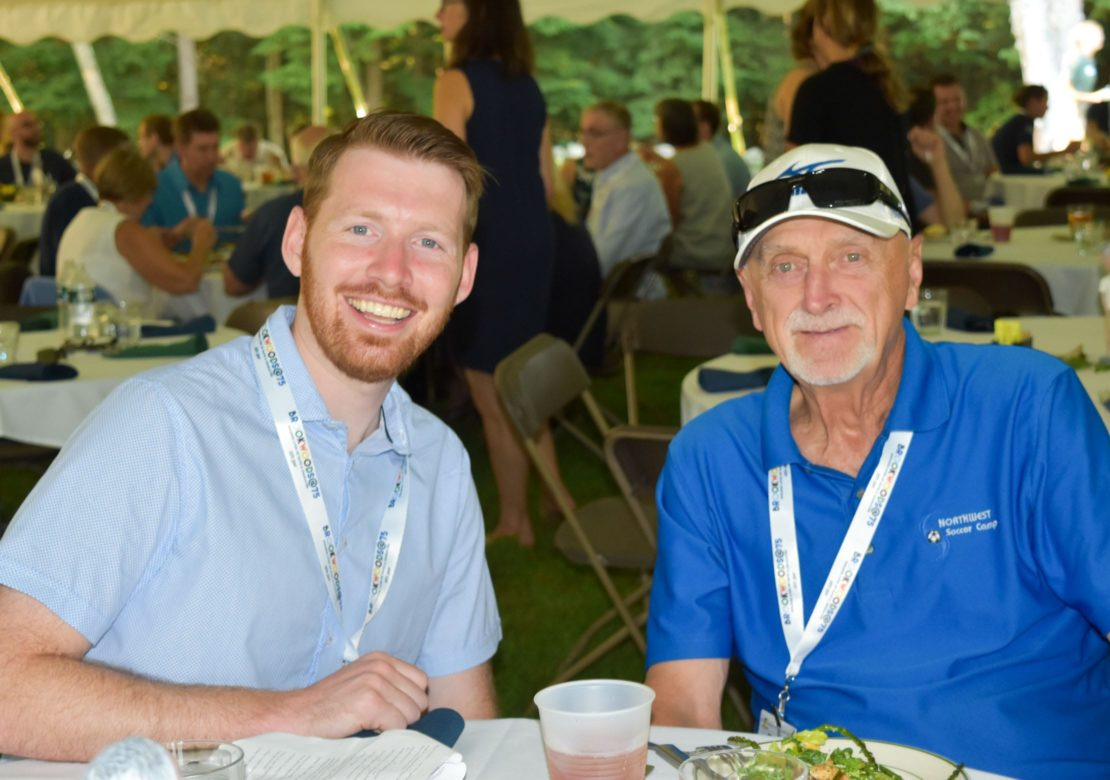 Young adult with an older man at an alumni event