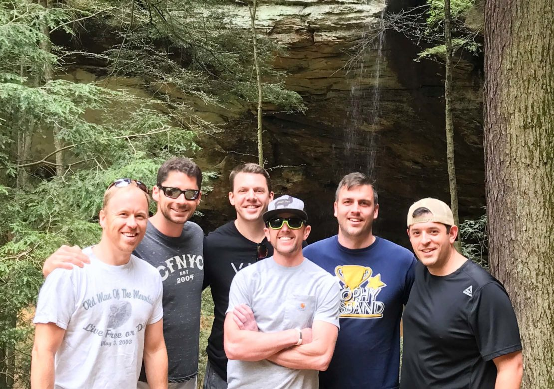Group of male almuni standing by waterfall