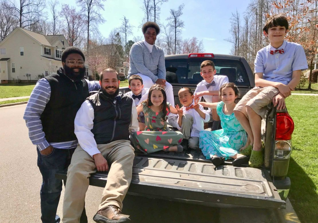 Alumni and family on pickup truck