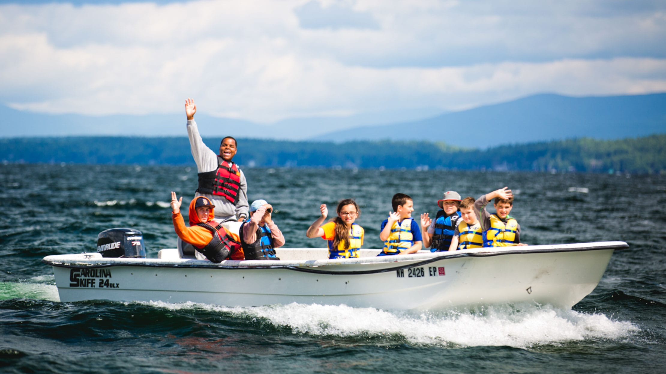 Campers on a motorboat giving a thumbs up