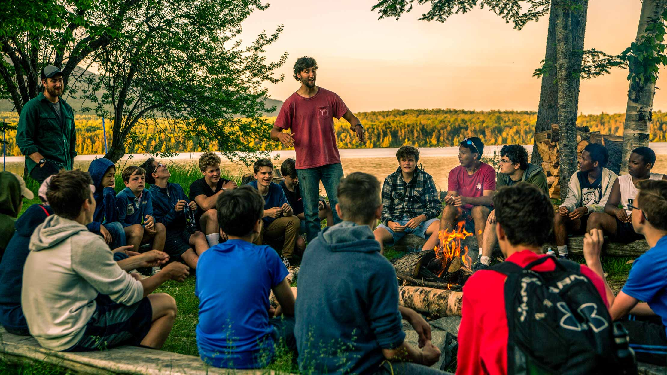 Staff at a campfire with campers sitting