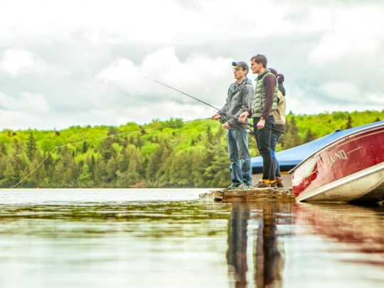 Adults fishing on a lake at Moose River Outpost