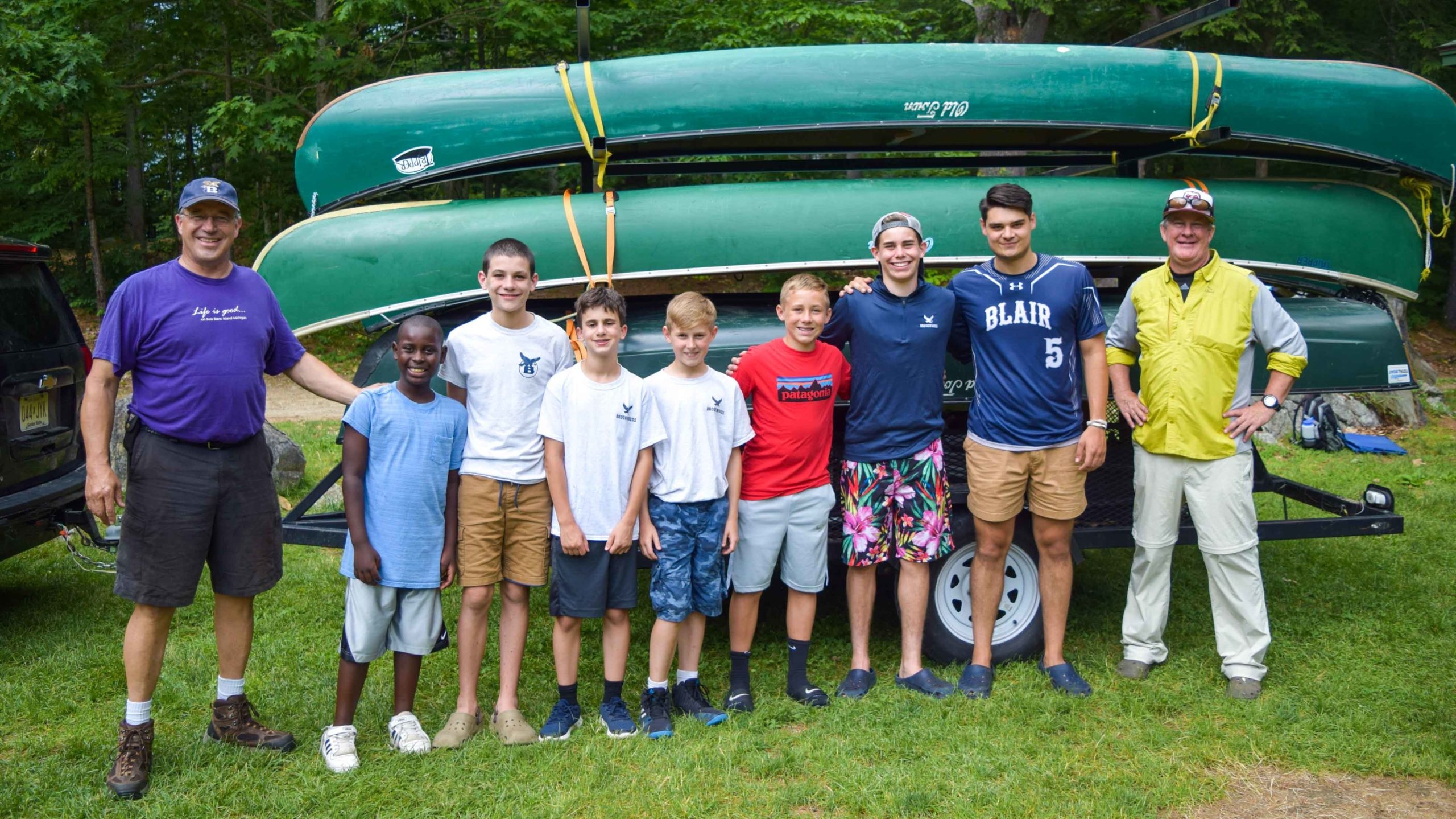 Staff and campers standing next to canoes